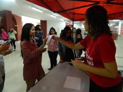 Imagem mostra alunos recebendo camisa da instituição