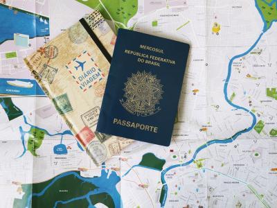 Imagem mostra um mapa, um caderno e um passaporte