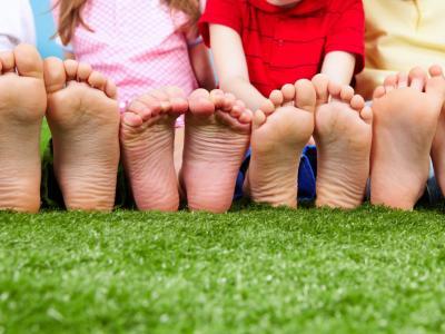 Imagem mostra pés de crianças sentadas na grama