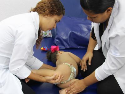 Imagem mostra criança recebendo atendimento fisioterápico