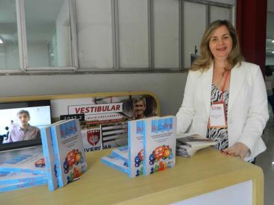 Imagem mostra professora durante o lançamento do livro