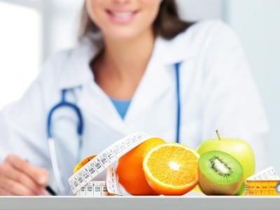Imagem mostra uma nutricionista sentada em uma mesa que tem frutas e uma fita métrica em cima