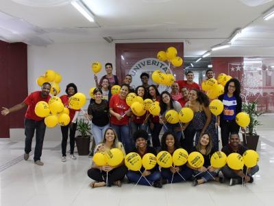 Imagem mostra estudantes com balões amarelos