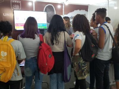 Imagem mostra estudantes em pé observando monitor