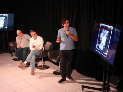 Imagem mostra professor em pé palestrando e outros dois sentados observando