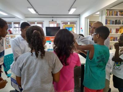 Imagem mostra crianças em sala sendo instruídas por adultos