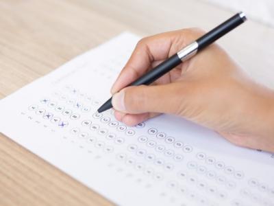 Imagem mostra mão segurando caneta e marcando gabarito