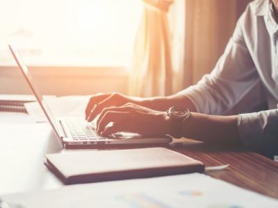 Imagem mostra mãos masculinas usando laptop