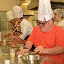 Imagem mostra jovem com Síndrome de Down produzindo massa de macarrão