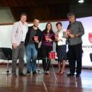 Imagem mostra cinco pessoas em pé no palco