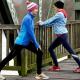Imagem mostra pessoas agasalhadas e se alongando antes da atividade física